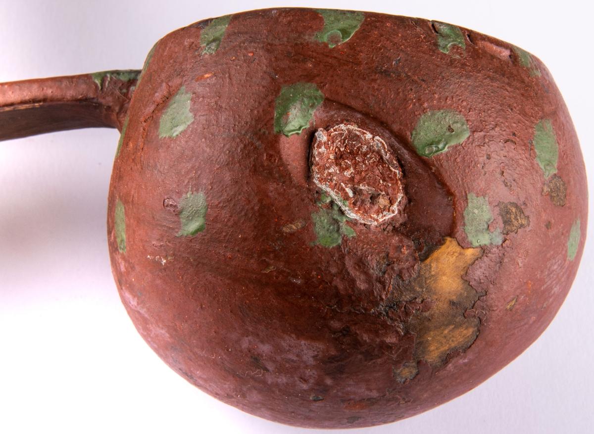 Acc.kat. Skopa av björkträ, naturvuxen. Rödmålad. Dekor: gröna prickar.  Ett hål i träet i sidan har lagats med ett metallmynt. Skaften ände helt omkrökt. Längd 19cm.