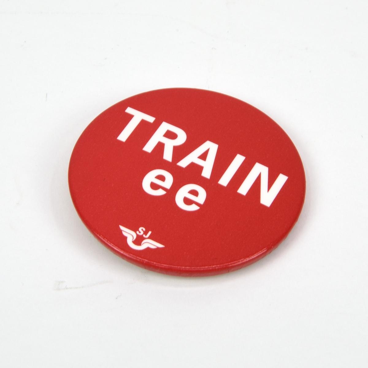 """Rund pin med texten """"TRAINee"""" i vitt mot röd botten. Under texten finns SJ:s logotyp. Baksidan består av vit plast med en infälld säkerhetsnål."""