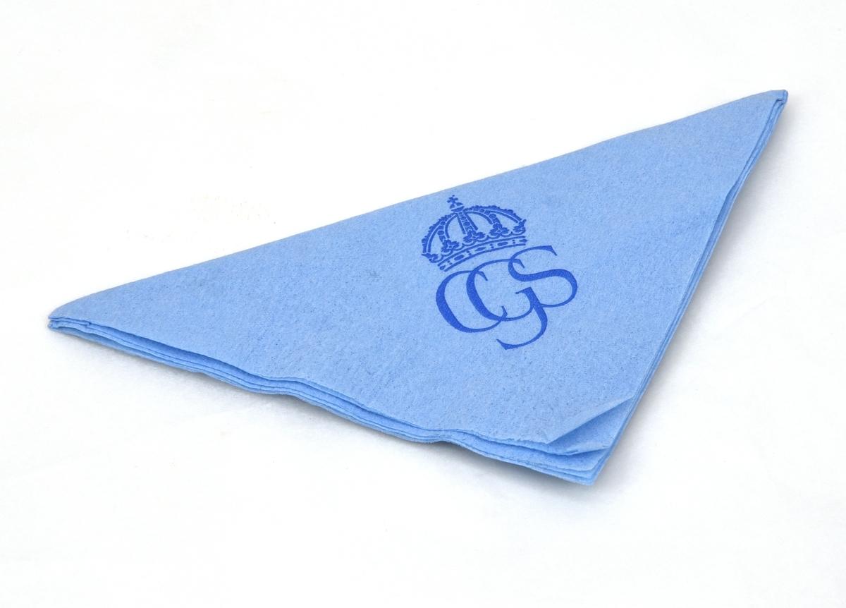 """Ljusblå kvadratisk pappersservett med det monogram som användes vid kungabröllopet 1976 tryckt i mörkblått. Monogrammet består av """"CGS"""" med en kunglig krona ovanför. Runt servettens kanter går en streckad bård med pärlstavsfris."""