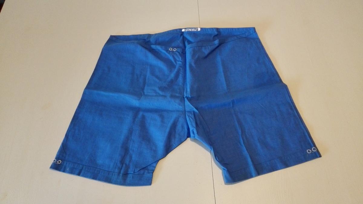 1 shorts.  Lårlange bukser m/løpegang i livet. Ringar for hol i løpegangen til træing av elastikk i liv og kring buksebein. Øvingsarbeid.