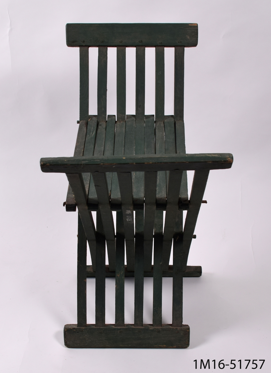 Grönmålad trädgårdstol utan ryggstöd, bestående av fyrsidiga träribbor och ihopfällbar från sidorna.    Neg.nr: 981/1051:2
