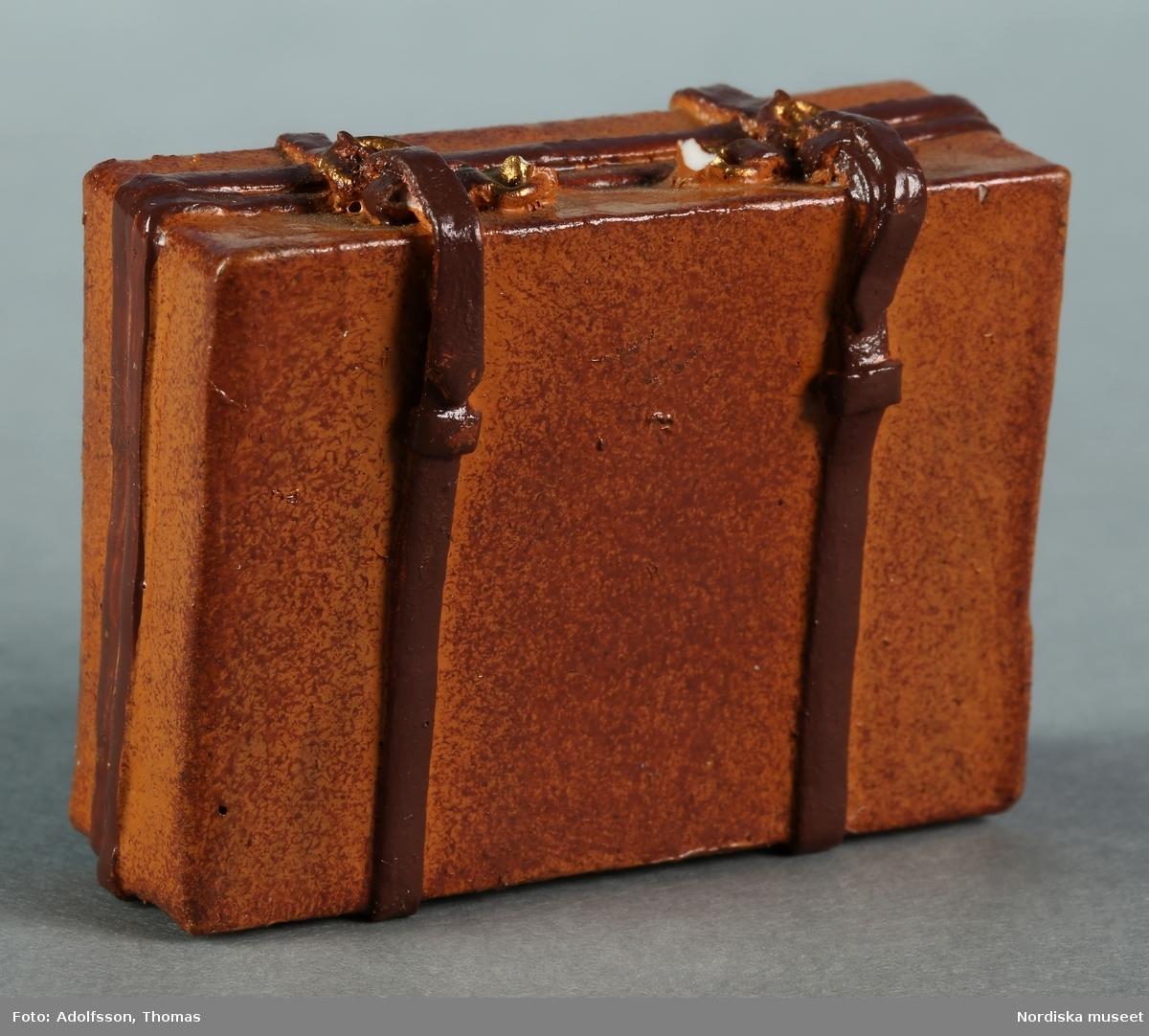 Resväska tillverkad av gips eller konstmassa och målad i två olika bruna nyanser. Ska stå i dockskåpets vindsutrymme.
