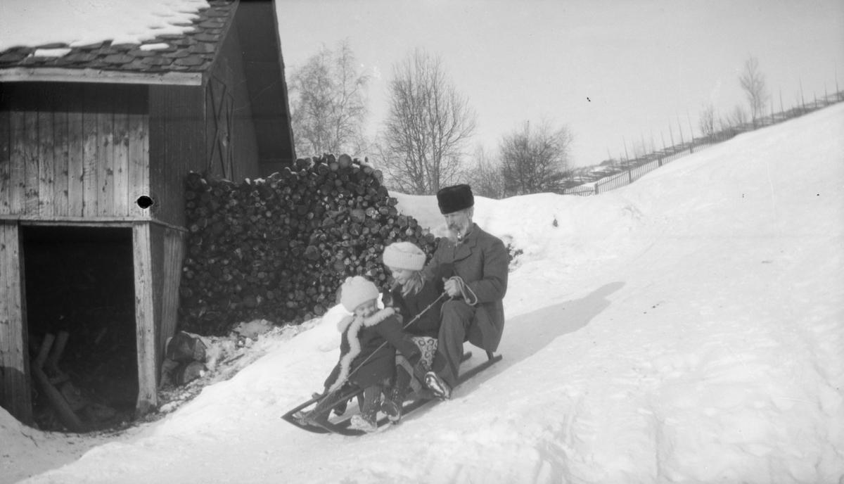 Mann og to barn på kjelkeaking