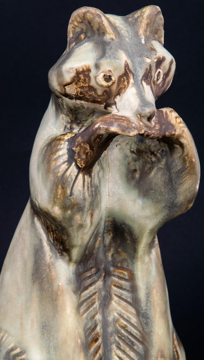 """Tvättbjörn av chamotte, skulpterad av Lillemor Mannerheim för Gefle Porslinsfabrik. Stående med framtassarna mot nosen. Original. Dekor, stengodsglasyr grön/brunskiftande. Signerad under med svart """"Lillemor -55 Gefle""""."""