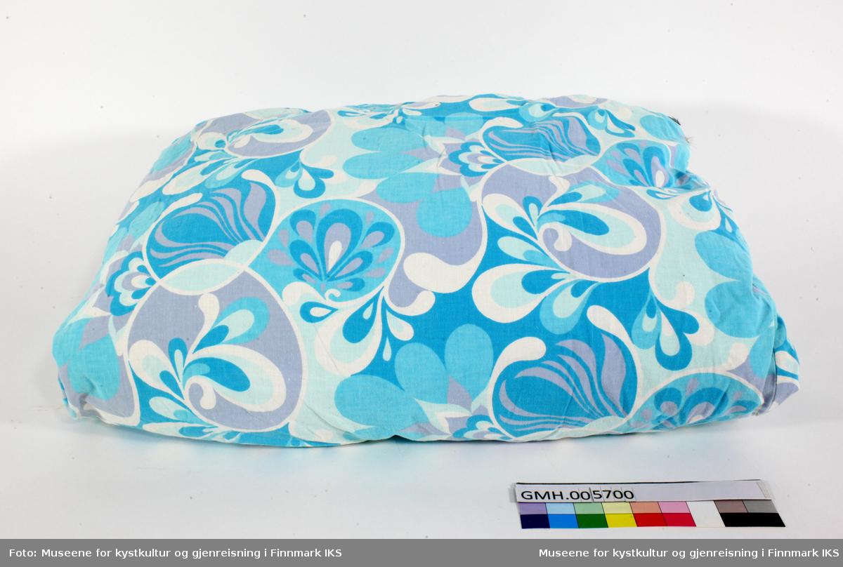 Tekstilene er knyttet til soverommet og kjøkken. Følgende tekstiler og utstyr tilhører soverom: - to puter - ei vattpute med blå og hvitrutet pute trekk og ei hodepute av dun uten trekk - ei utslitt dundyne  der teppetrekket er sydd på for å holde duna på plass. Dynetrekket har blå blomster på hvit bunn  - dynetrekk i rosa blomster/roser med små grønne blad på hvit bunn som er reparert/lappet . På teppetrekket har giver festet en lapp med nål. - dyne/teppetrekk gul og hvitrutet mønster - putetrekk, hvit (nyinnkjøpt) - emballasjen merket Dale Flanell, Sengetøy i ren bomull. Med prydsøm, Made in Norway - nattkjole, røde prikker på hvit bunn og med skulderhemper. Følgende tekstiler tilhører kjøkken: - to heklede grytekluter (par) - firkantede, avrundede hjørner  med  fire små hjørner vekselsvis i lys grønt og lys gult med hempe i et av hjørnene. - et heklet firkantet håndkle (lite) med gul bunn og grønn kant med hempe i det ene hjørnet. - to forklær, et gult med to lommer med hvit lilla, grønn og oransje farger med grønn bord nede og rundt lommene og et oransje forkle med storrutete lommer og kant oppe og nede. Forklærne knyttes rundt livet. I tillegg er det ei sofapute, brodert i ullgarn med brunrutet kant og trekanter inn mot midten og hjerteliknende hjørner i flere farger og et korsliknende midtparti med farger som hjertene. Den indre rammen har grå bunn. Ei vattpute er trolig sydd inn.