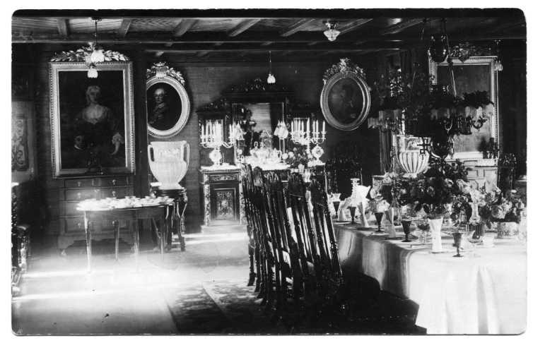 Interiör från Grand Hotell Ribbagården. Historiska porträtt i breda ramar på väggarna, höga stolar runt dukat bord.