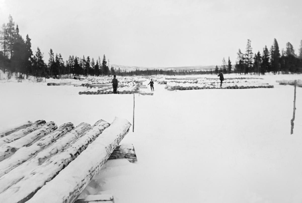 Tømmer på den islagte og snødekte kanalen mellom Aursjøtjern og Grøna i Elvdalen i Engerdal.  De barkete tømmerstokkene er lagt i floer på isen i påvente av merking.  Tre mann i bakgrunnen, en er skiløper, de to andre kan vøre skogsarbeidere eller merkere.  Landskapet omkring kanalen er kledd med furu- og bjørkeskog.