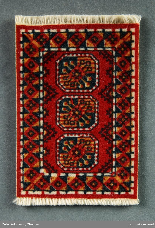 Wiltonmatta med orientaliskt tryckt mönster i röda nyanser. Hör till soffgruppen (NM.0333279 a-c) i hallen på första våningen i dockskåpet NM.0331721+.