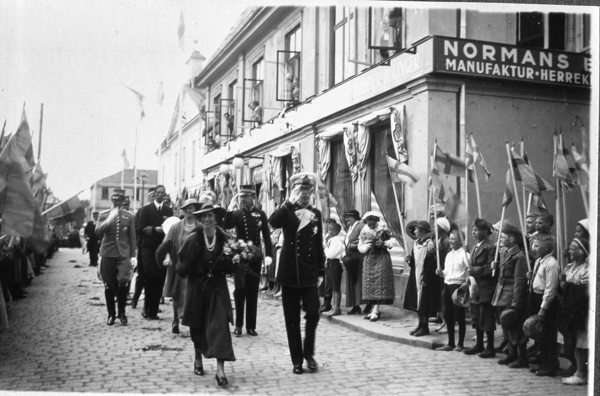 Stora delar av den kungliga familjen är i Arboga för att fira Sveriges Riksdags 500-årsjubileum. Här promenerar de, från Rådhuset, mot Heliga Trefaldighetskyrkan. Främst går kronprinsessan Louise tillsammans med svärfar, Gustaf V, som gör honnör. Prinsessan har vidbrättad hatt, halsband och en stor blomsterbukett i famnen. Bakom dem går prinsessan Sibylla tillsammans med sin svärfar; kronprins Gustaf Adolf. I tredje raden kommer prins Gustaf Adolf, i uniform, bredvid sin farbror prins Wilhelm. Skolungdomar kantar Rådhusgatan och vinkar med svenska flaggor. En kvinna i folkdräkt syns på trottoaren utanför Normans manufaktur. (Arbogautställningen pågår samtidigt och kungen hinner med ett kort besök även där).