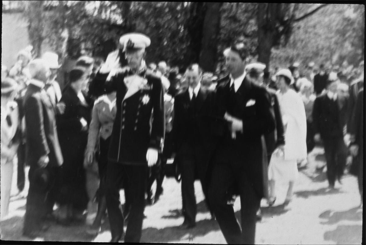 Kung Gustaf V, och en stor del av den kungliga familjen, är i Arboga med anledning av Sveriges Riksdags 500-årsjubileum.  Här är konungen på väg in i Heliga Trefaldighetskyrkan tillsammans med borgmästare Wilhelm Wester. Borgmästarinnan syns en bit bakom honom, i ljusa kläder. Publiken kantar vägen.