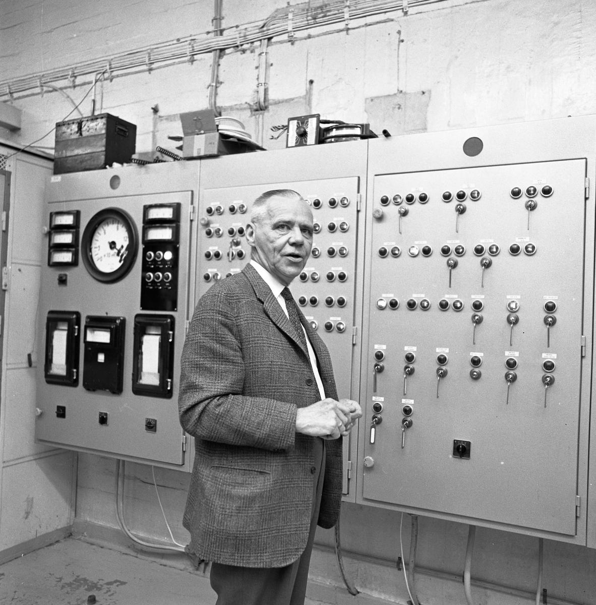 Alf Hedlund, maskinmästare på Centrala Verkstaden Arboga, går i pension  Kostymklädd man i industrimiljö. Knappar och reglage.