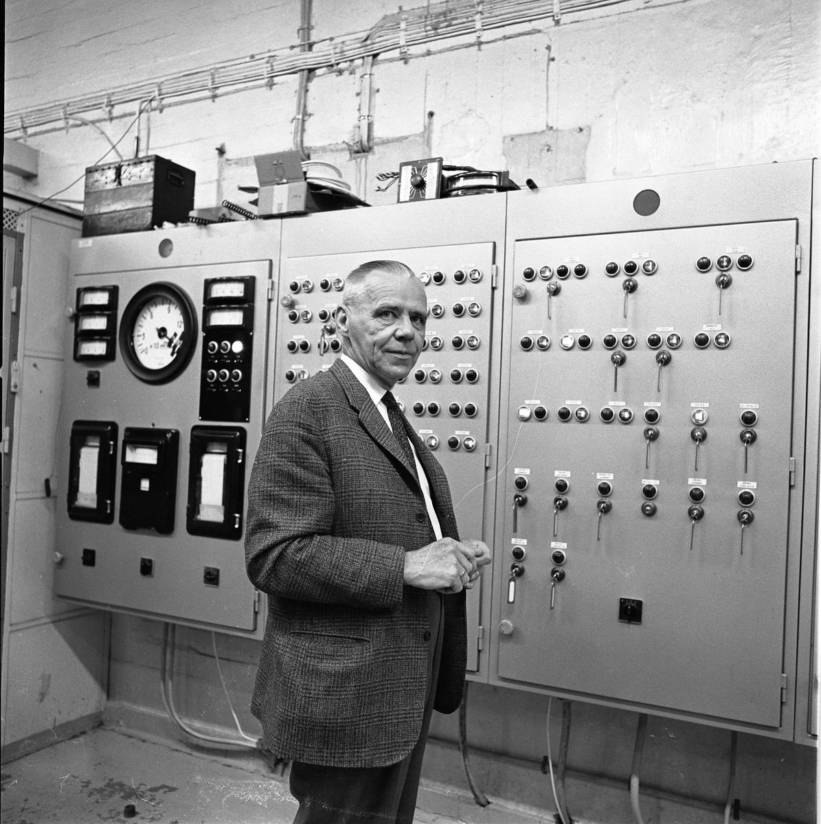 Alf Hedlund, maskinmästare på Centrala Verkstaden Arboga, går i pension  Kostymklädd man i industrilokal. Knappar och reglage.