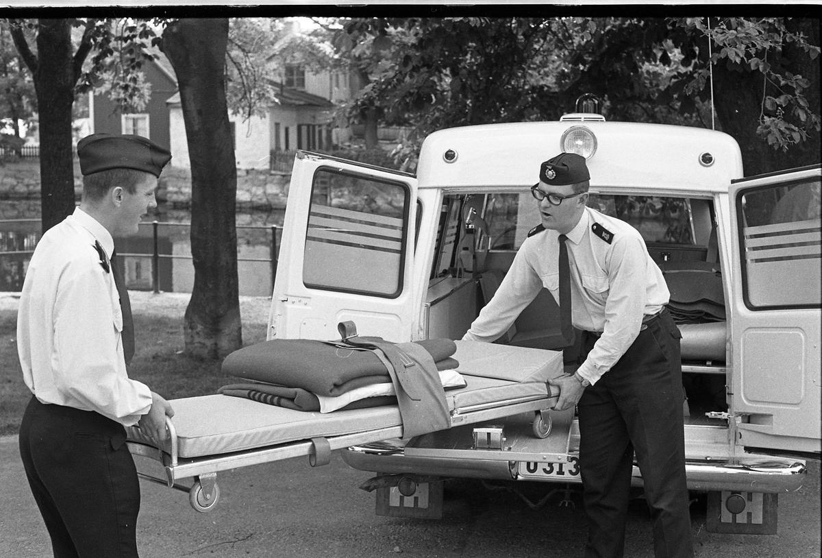 """Bengt """"Kos"""" Svensson (till vänster) och Tage Andersson (till höger) drar ut bårvagnen ur den nya ambulansen. Både Bengt och Tage är deltidsanställda på ambulansen. Den nya ambulansen ersätter den som krockade i olyckan på Annandag Pingst.  Två uniformsklädda män och en ambulans. Bilden är tagen på Strandvägen."""