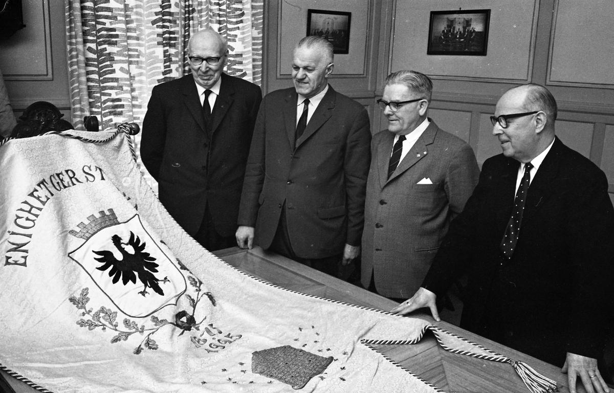"""Fyra kostymklädda män ser på en fana med texten """"Enighet ger styrka"""". Från vänster: Gustav Johansson (Murar-Gustav), Holger Eklöf, Axel Fritiof Strandberg (Atchy) och okänd. De befinner sig i Arbetareföreningens lokal. Interiör."""