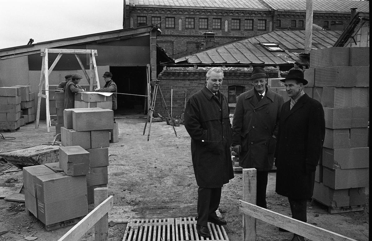 Arboga bryggeri bygger egen bilverkstad med två portar. Tre män, i ytterrockar, står i en byggarbetsplats. Bryggeriet syns i bakgrunden. Från vänster: bryggerichef Karl Ivar Levert, bryggmästare Ture Anderberg och okänd.  Anläggningen var färdigbyggd 1899 och verksamheten startade 1 november samma år. 24 oktober 1980 tappades det sista ölet, på bryggeriet. Märket var Dart. Läs om Arboga Bryggeri i hembygdsföreningen Arboga Minnes årsbok 1981