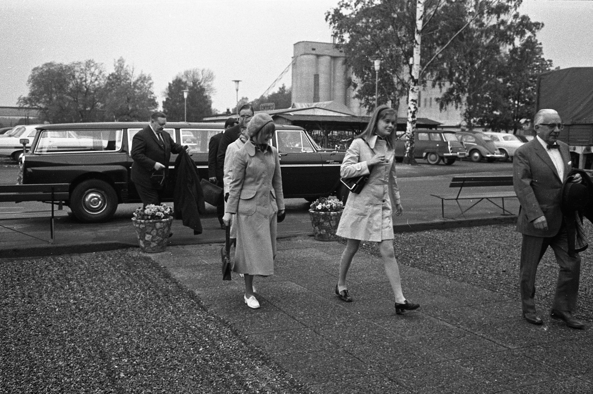 Arboga Maskiner levererar jubileumsmaskin till kund, 1970-talet. Finklädda män och kvinnor har anländ med limosin och är på väg in till Arboga Maskiner. Männen bär kostym och kvinnorna har ytterkläder på sig.  Limosinen är en Checker Aerobus Convoy. På parkeringen syns en SAAB, en folkvagn och en Amazon. Centralföreningens silo ses i bakgrunden.  AB Arboga Maskiner startade 1934 och tillverkar borr- och slipmaskiner.