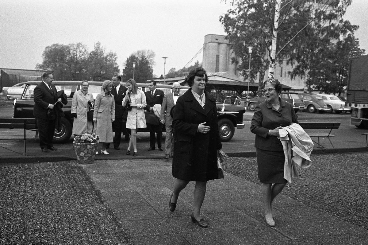 Arboga Maskiner levererar jubileumsmaskin till kund, 1970-talet Finklädda män och kvinnor har anlänt med limosin. Männen bär kostym och kvinnorna har ytterkläder på sig. De är på väg in till Arboga Maskiner. Limosinen är en Checker Aerobus Convoy. På parkeringen står en SAAB, en Wolksvagen och en Amazon. Centralföreningens silo skymtar i bakgrunden.  AB Arboga Maskiner startade 1934 och tillverkar borr- och slipmaskiner.