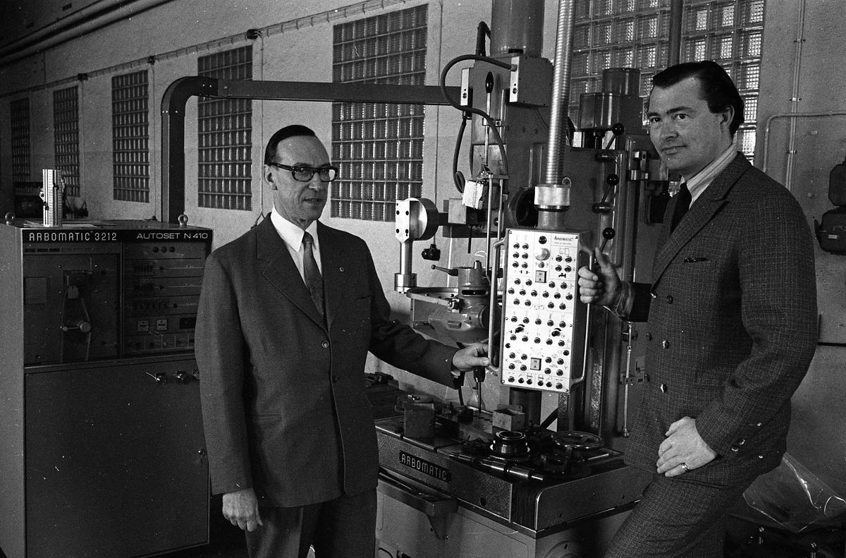 Arboga Maskiner levererar jubileumsmaskin till kund, 1970-talet. Två kosymklädda män står intill en maskin märkt Arbomatic. De befinner sig i fabriksmiljö.