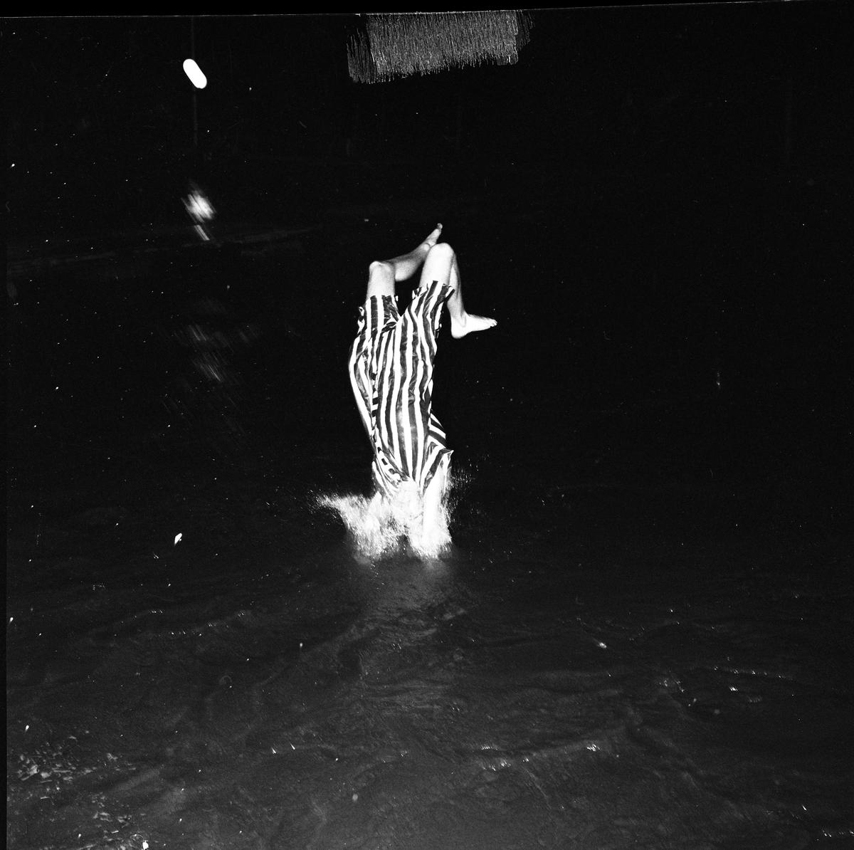 Arboga Simsällskap arrangerar Eldfest vid Villagatsbadet. En man, i randig baddräkt, dyker i vattnet.