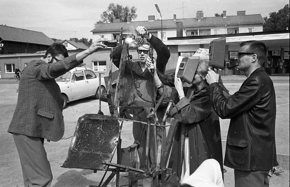 Arboga Tekniska Skola, skändning av nya elever. Svetsning pågår. I bakgrunden syns bilar, Texacos bensinstation och hyresfastigheten på Bergmans gränd.