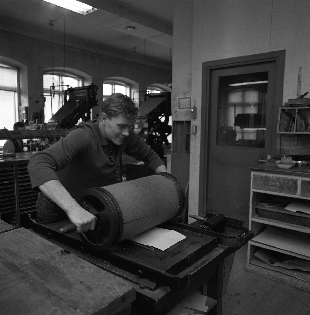 Arboga Tidning, personal och interiör. En man med en vals. I bakgrunden syns flera maskiner, en arbetsbänk och en dörr till ett annat rum.