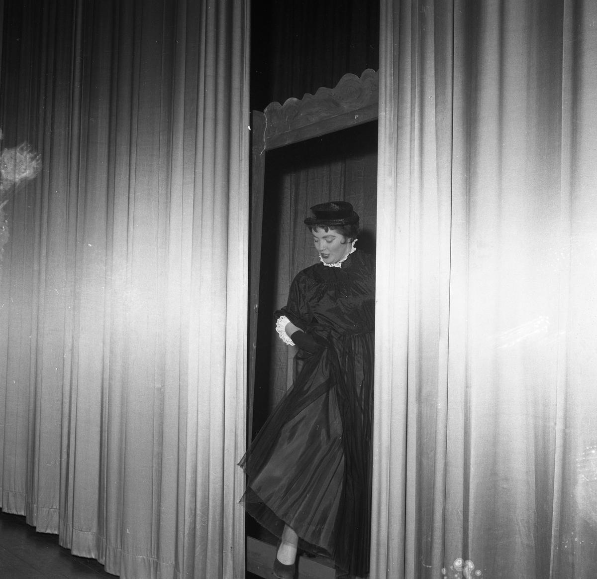 Arbogarevyn spelar upp sin Jubileumsrevy. En kvinna, i hatt och klänning, kliver in på scenen mellan ridåerna.