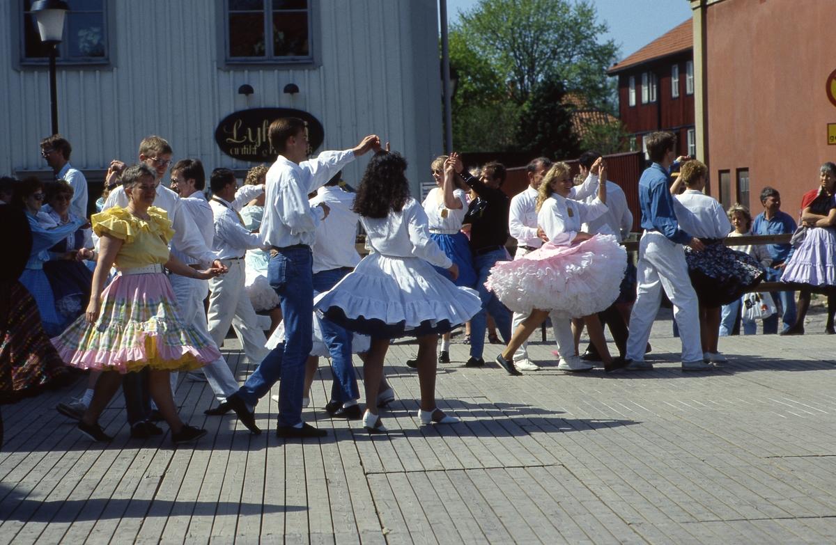 Arbogaträffen Square dance-uppvisning på ett uppbyggt dansgolv på Stora torget. Kvinnorna har vida kjolar och underkjolar. I bakgrunden syns butik Lyktan.