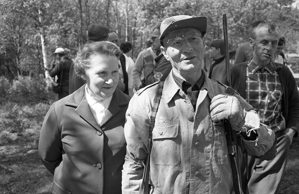 AT-skytte Man med gevär på axeln. En kvinna står intill honom. Bakom paret syns flera människor. De befinner sig  i skogen. (AT kan betyda Arboga Tidning)