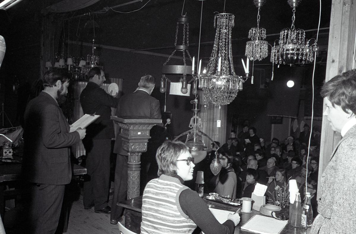 Auktion i Valskog. På scenen är många människor sysselsatta; en kvinna sitter och för anteckningar, en man står med en lista i handen, en man håller upp föremål för publiken och auktionsförrättaren talar för varan. Över scenen hänger kristallkronor och andra lampor. Det ser fullsatt ut i lokalen. Publiken sitter och står. De har ytterkläder och huvudbonader på sig.