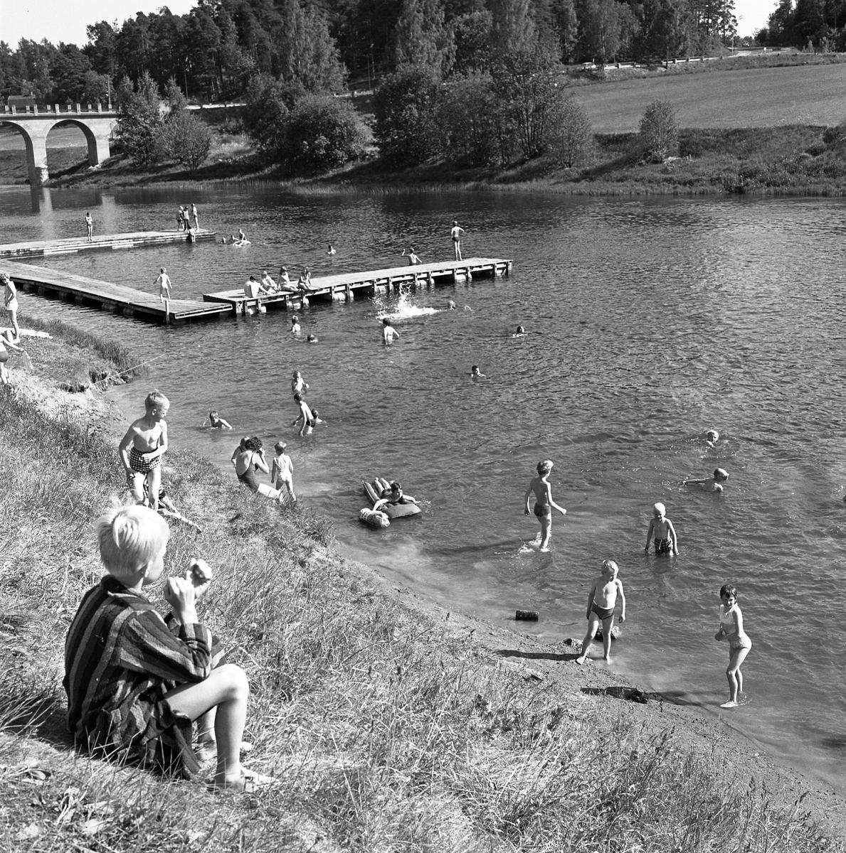 Barn som badar vid Villagatsbadet. Badbryggor i Arbogaån. Västerbron till vänster.