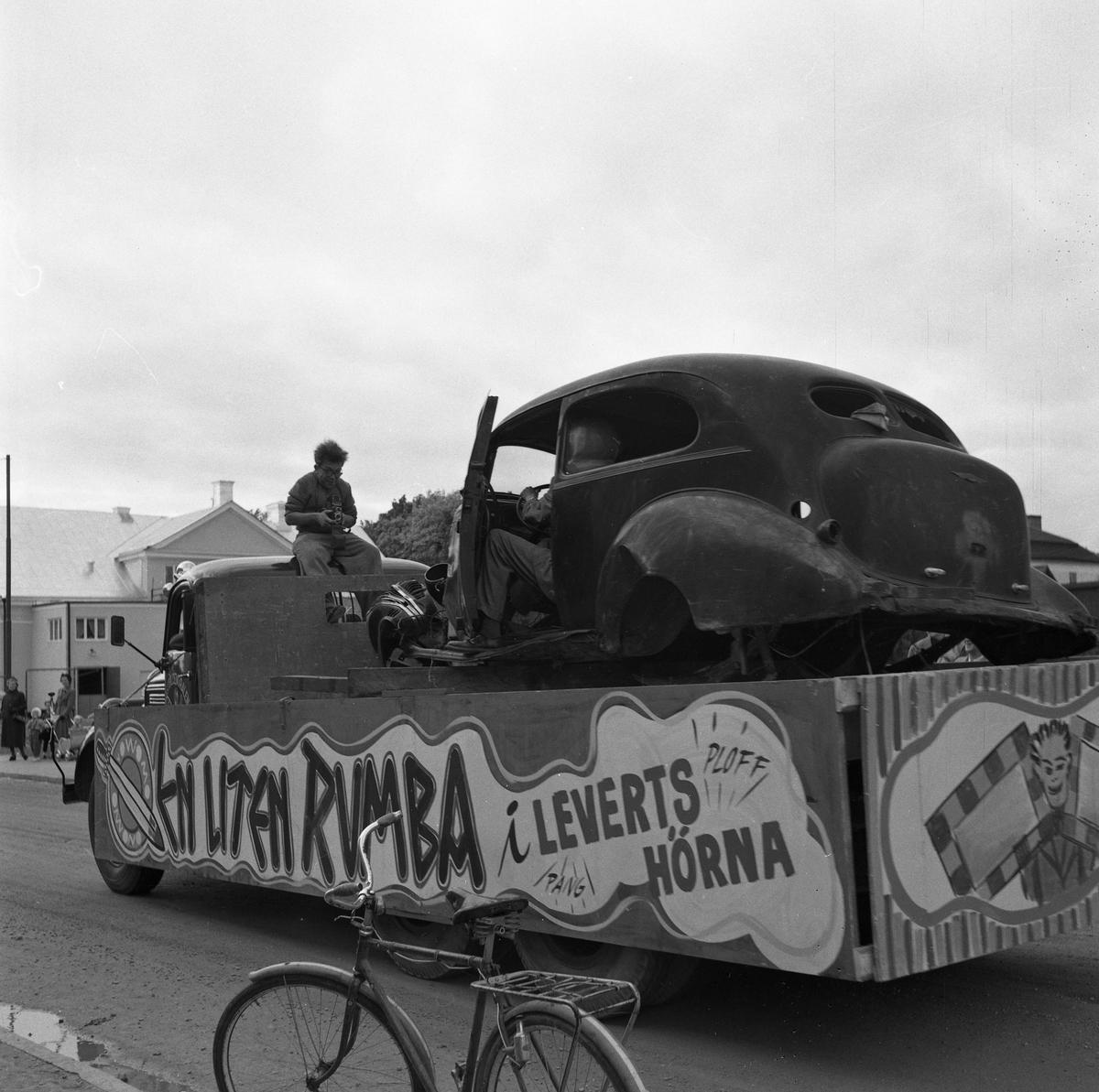 """Barnens Dag firas med en parad genom staden. Här är en lastbil som kör runt med en havererad bil på flaket och fotograf Lasse Åhlin sittande ovanpå hytten. """"En liten rumba i Leverts hörna"""" står det längs flaket. I Levert hörna skedde en del trafikolyckor, därav texten. Lasse fick ofta uppdrag, av polisen, att ta bilder på trafikolyckor."""