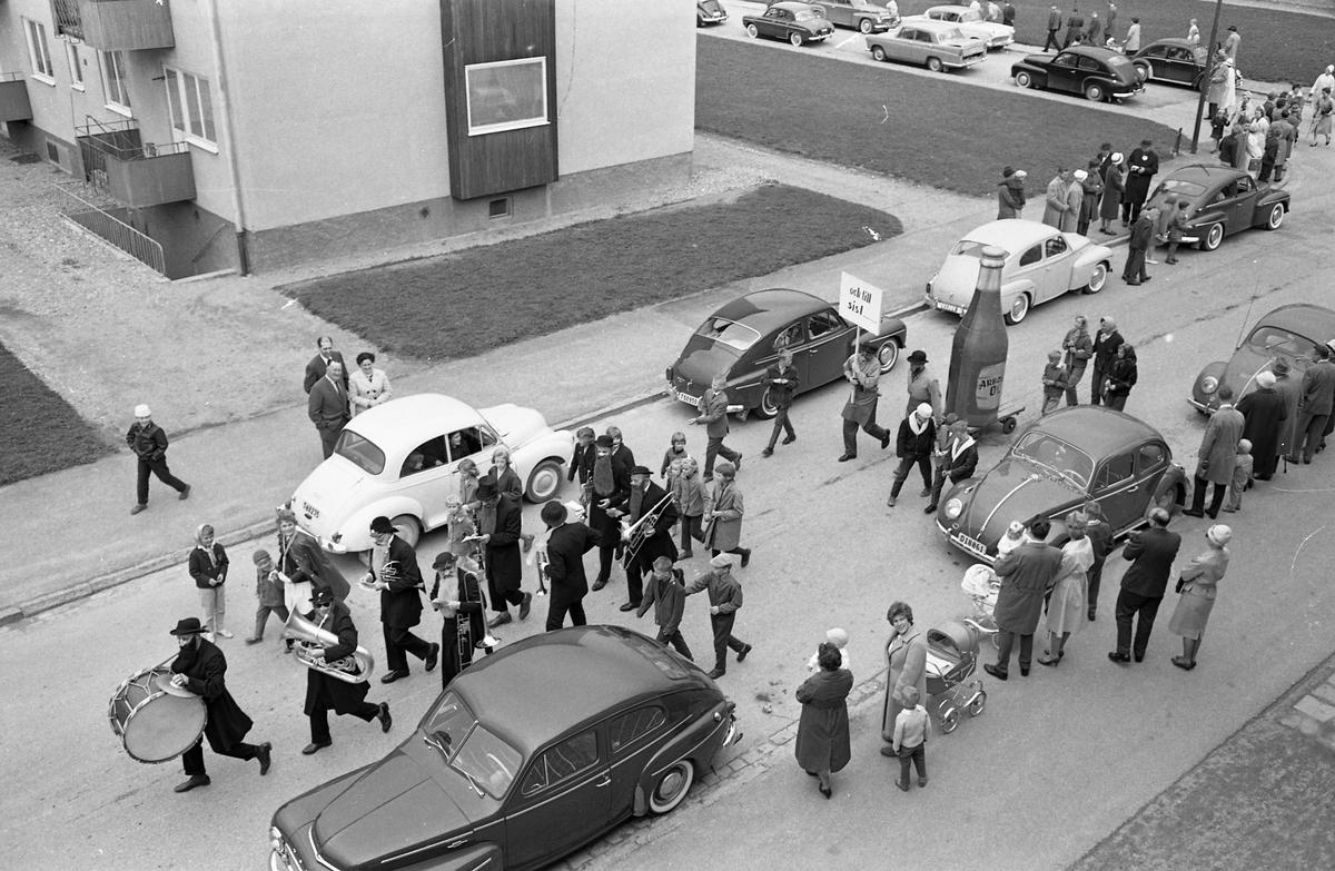 Barnens Dag firas med en parad genom staden. På Österled kommer en blåsorkester vars medlemmar har svarta hattar och långa skägg. Barnen sluter upp. Och till sist, kommer efter - som Arboga öl. Bilar står parkerade efter vägen och människor står på trottoaren och ser på. Orkestermedlemmarnas namn finns på bild 01518.