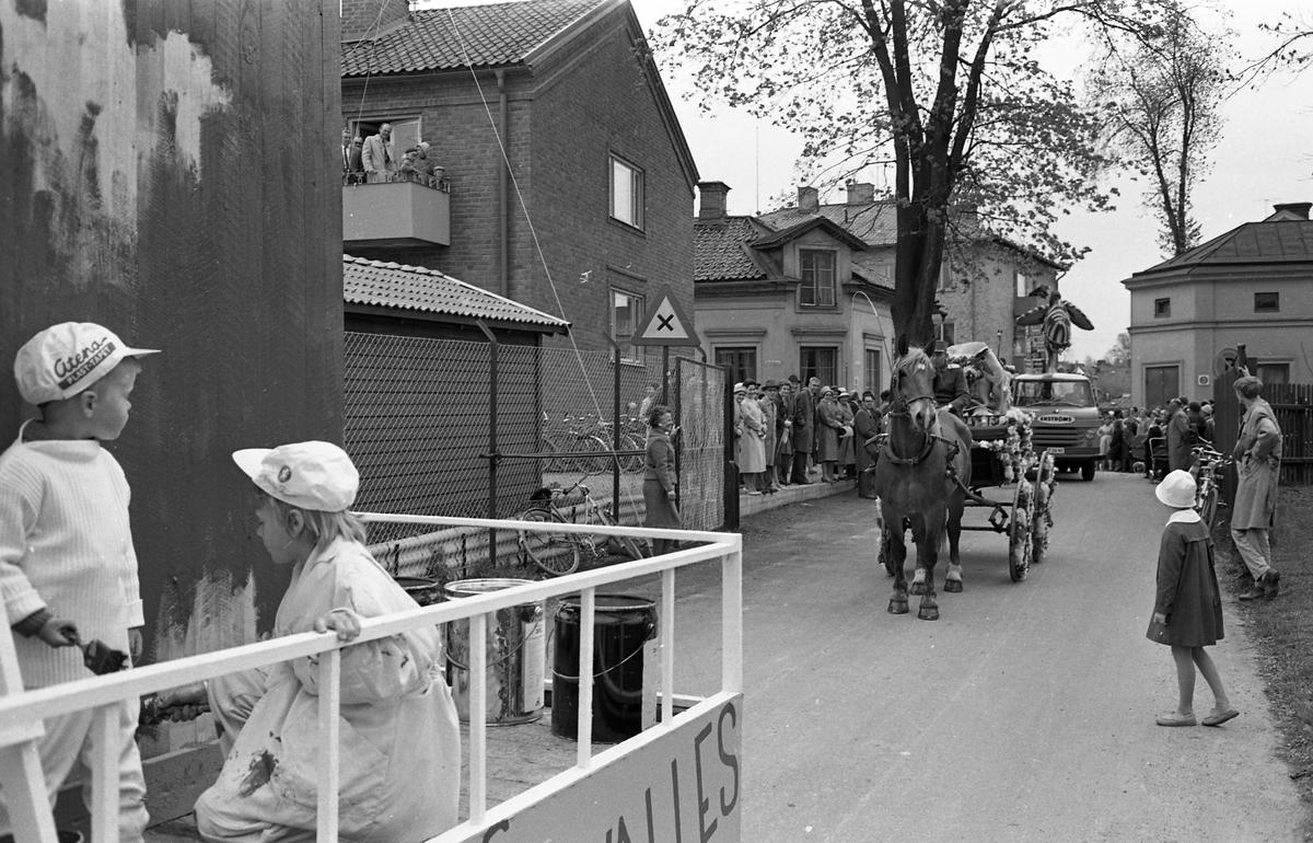 Barnens Dag firas med kortege genom staden. Närmast i bild åker en lastbil som gör reklam för Walles färg. Därefter kommer ett ekipage bestående av häst och vagn. Publik kantar vägen.