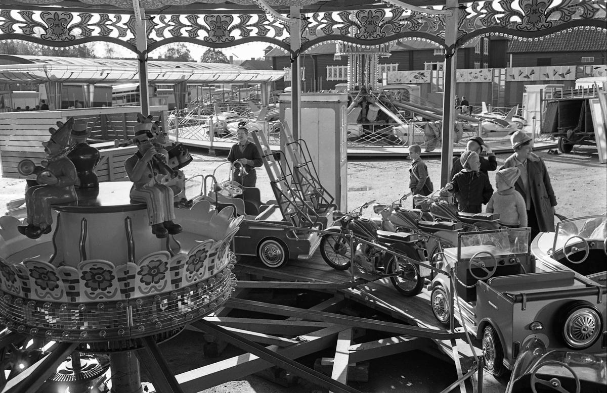Karusell på Björkmans Nöjesfält på Hamntorget. Några barn tittar på.