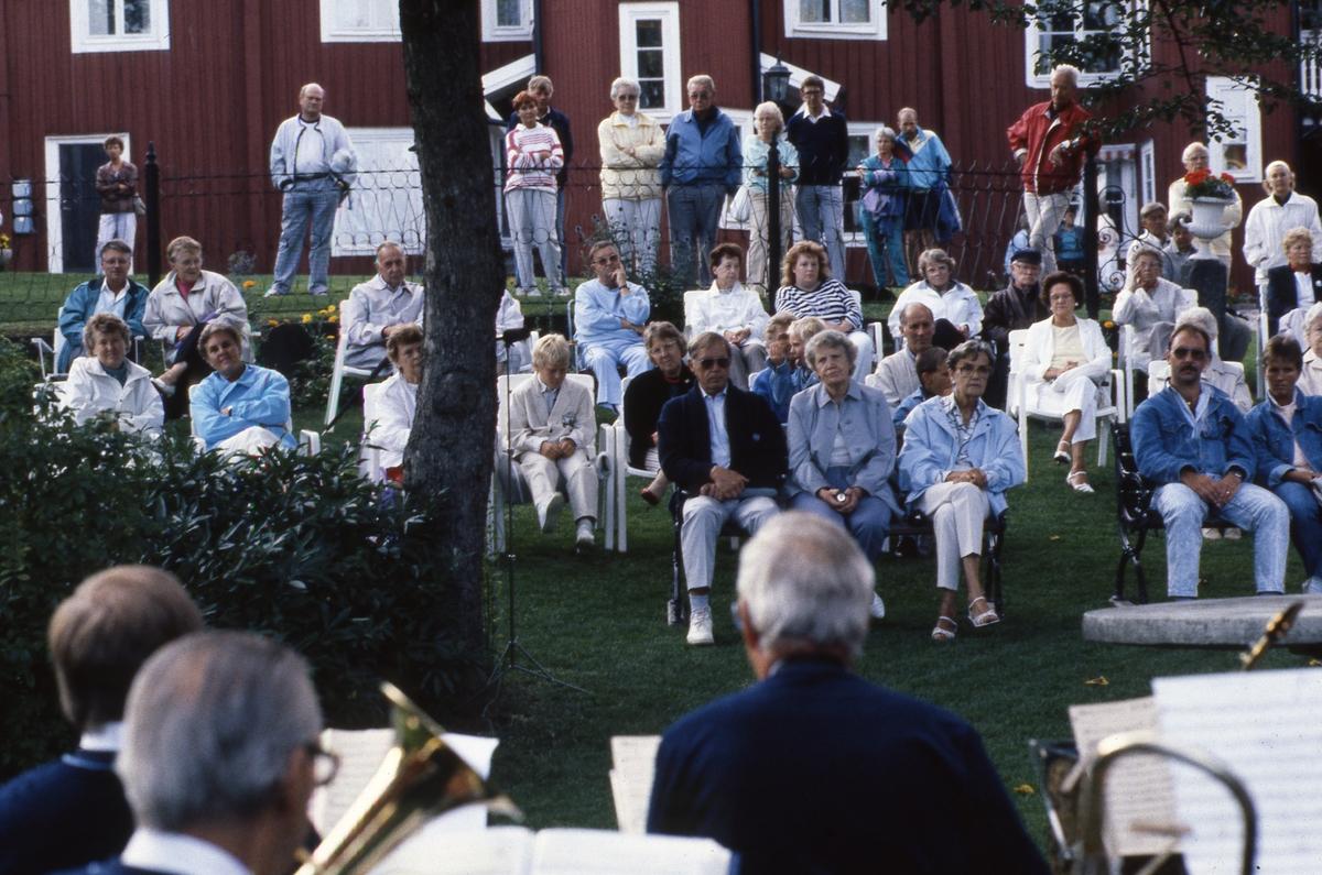 En blåsorkester uppträder i trädgården till Västerlånggatan 1. Publiken sitter, i trädgårdsmöbler, i slänten. Till vänster, bakom staketet, står Lars-David Hamrelius (ljus jacka och rutiga byxor). Med ryggen mot staketet sitter Britta och Sten Waldemarsson (hon i ljus jacka och han i mörk jacka och blå keps)