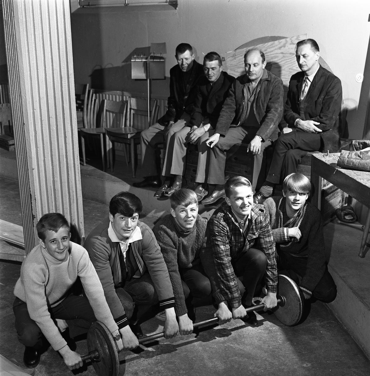 """Brottarkillar i träningslokalen. Grabbarna är, från vänster: Jan """"Pyrre"""" Nyberg, Christer """"Molla"""" Molin, Leif Andersson, Lars Hinrich och Roger """"Sluggo"""" Haglund.  Bakom dem sitter, från vänster: John Andersson, Boy Hinrich, Sam Nilsson och Börje """"Osten"""" Sjöberg. Arboga Atletklubb"""