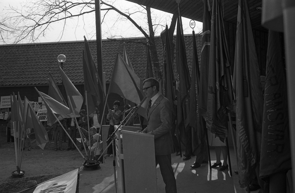 Första maj. En talare på scenen i Olof Ahllöfs park. Han är omgiven av fanor på scenen. Nedenför scenen står några pojkar med flaggor.