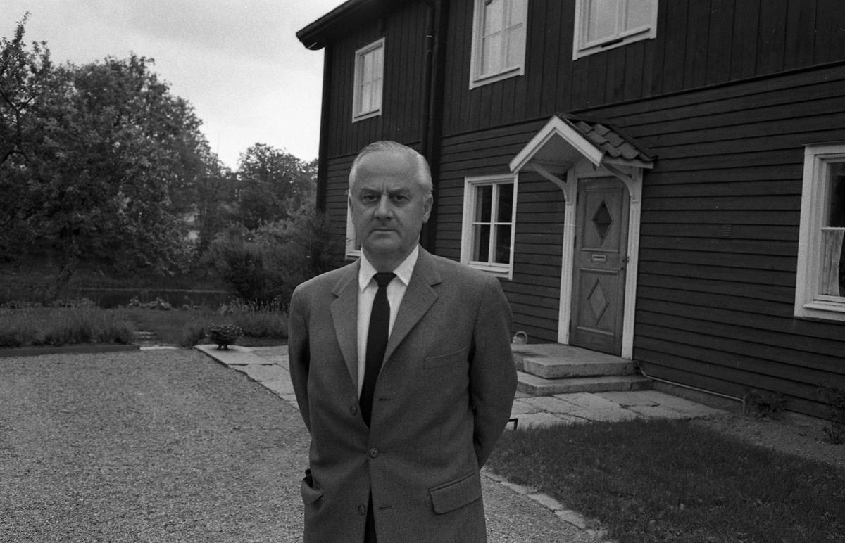 Doktor Bergquist/Bergkvist/Bergqvist Man i kostym och slips. Han står framför ett boningshus. Ett vattendrag syns i bakgrunden.