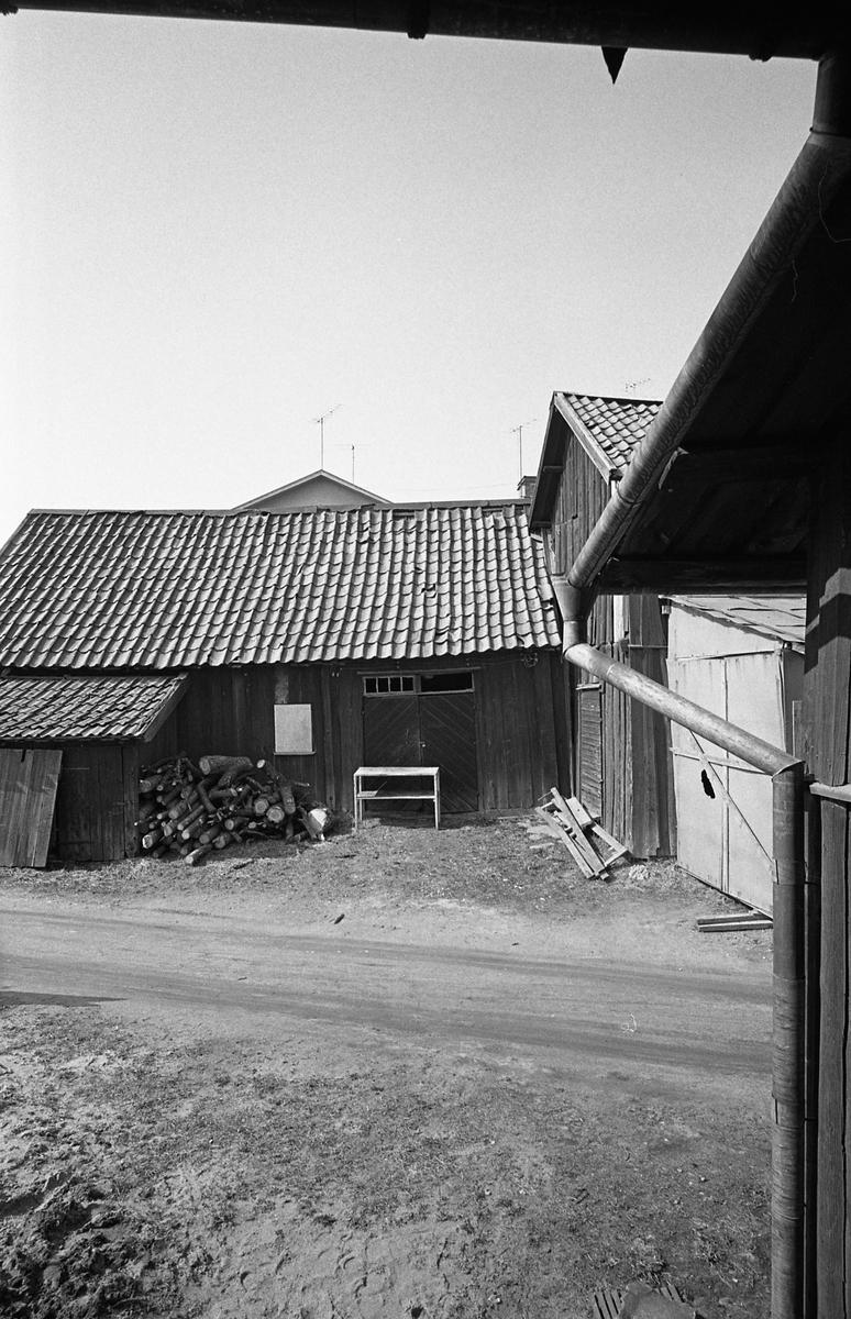 Innegård. Här ligger ved att kapa, intill uthusen. Äldre bebyggelse. Miljö. Fotografens anteckningar: Dokumentation av fastigheter i kvarteren söder och norr om ån. Bilder och beskrivning finns på Arboga Museum.
