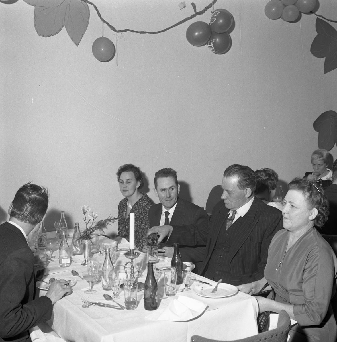 Elektrikerförbundets Arbogaavdelning har jubileumsfest. Män och kvinnor som just avslutat en måltid. Bordet är dukat med en ljusstake och en vas med en blomma. Väggdekorationer. Kvinnan, vid bordet bakom, är fru Bergström.
