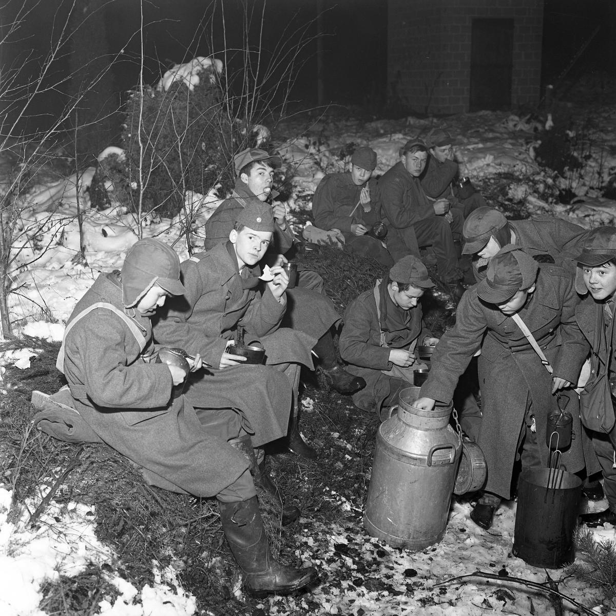 FBU-ungdomar övar.  Unga pojkar sitter på granris och äter. De är klädda i yllerockar och mössor med öronlappar. Det är vinter och snö. De äter ur sina plåtburkar. En stor mjölkkanna är placerad framför dem. FBU betyder Frivillig befälsutbildning