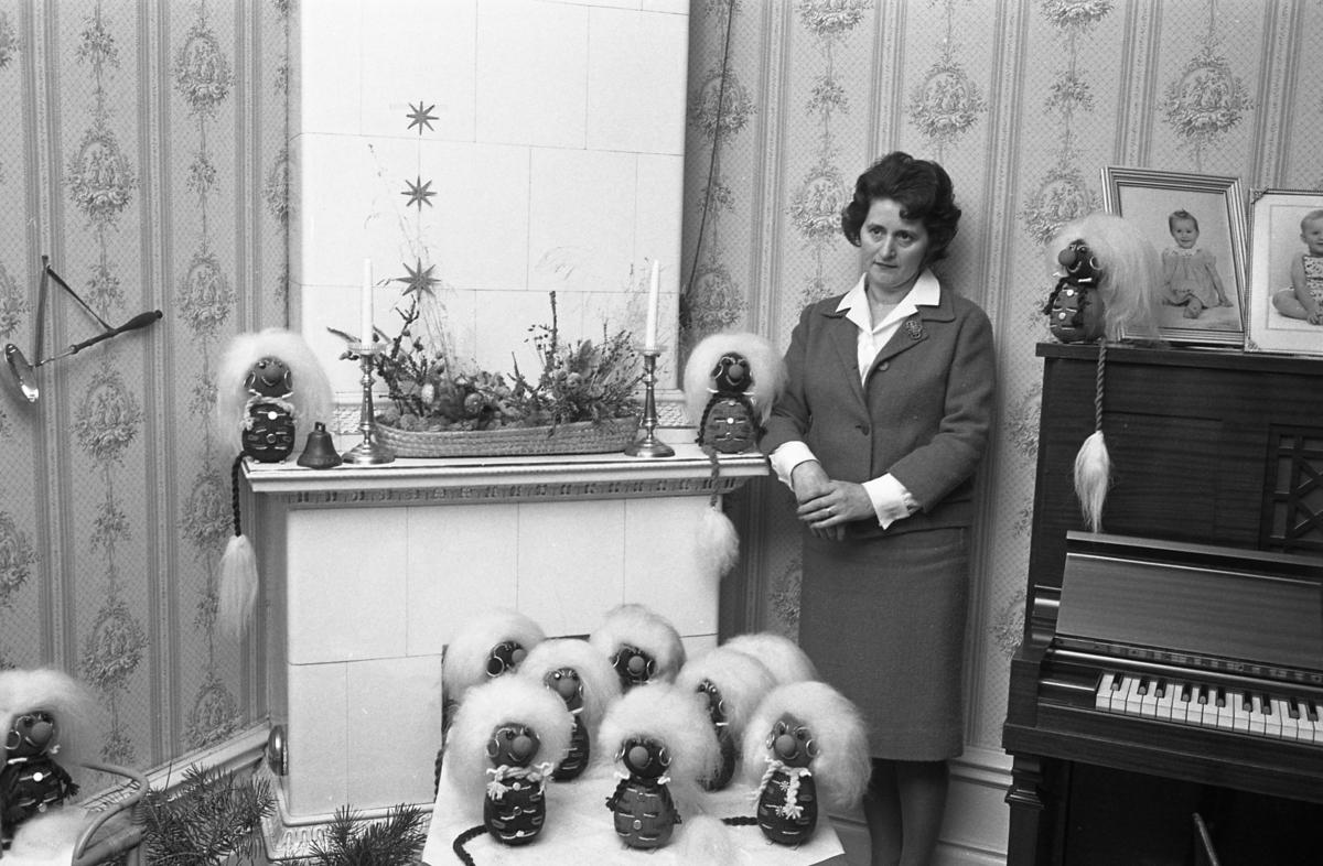 """Fru Margit Gillberg i Hagbylund i Medåker är en """"pysslare"""". Hon gör troll och korgar som hon skänker bort i present. Margit bär en dräkt med en brosch på slaget. Hon står intill kakelugnen. Hennes troll står uppradade. Intill henne står ett piano med fotografier ovanpå."""