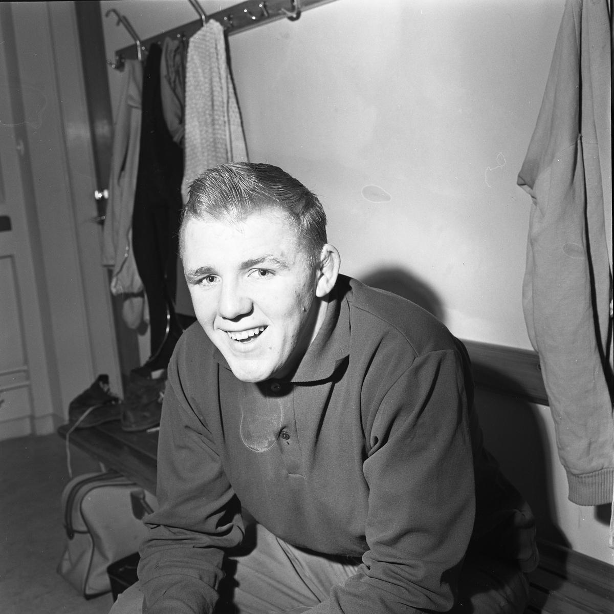 Roland Andersson deltar i fyrstadsbrottningen; Arboga - Eslöv - Uddevalla och Falkenberg Porträtt av ung man som sitter på en bänk i omklädningsrummet