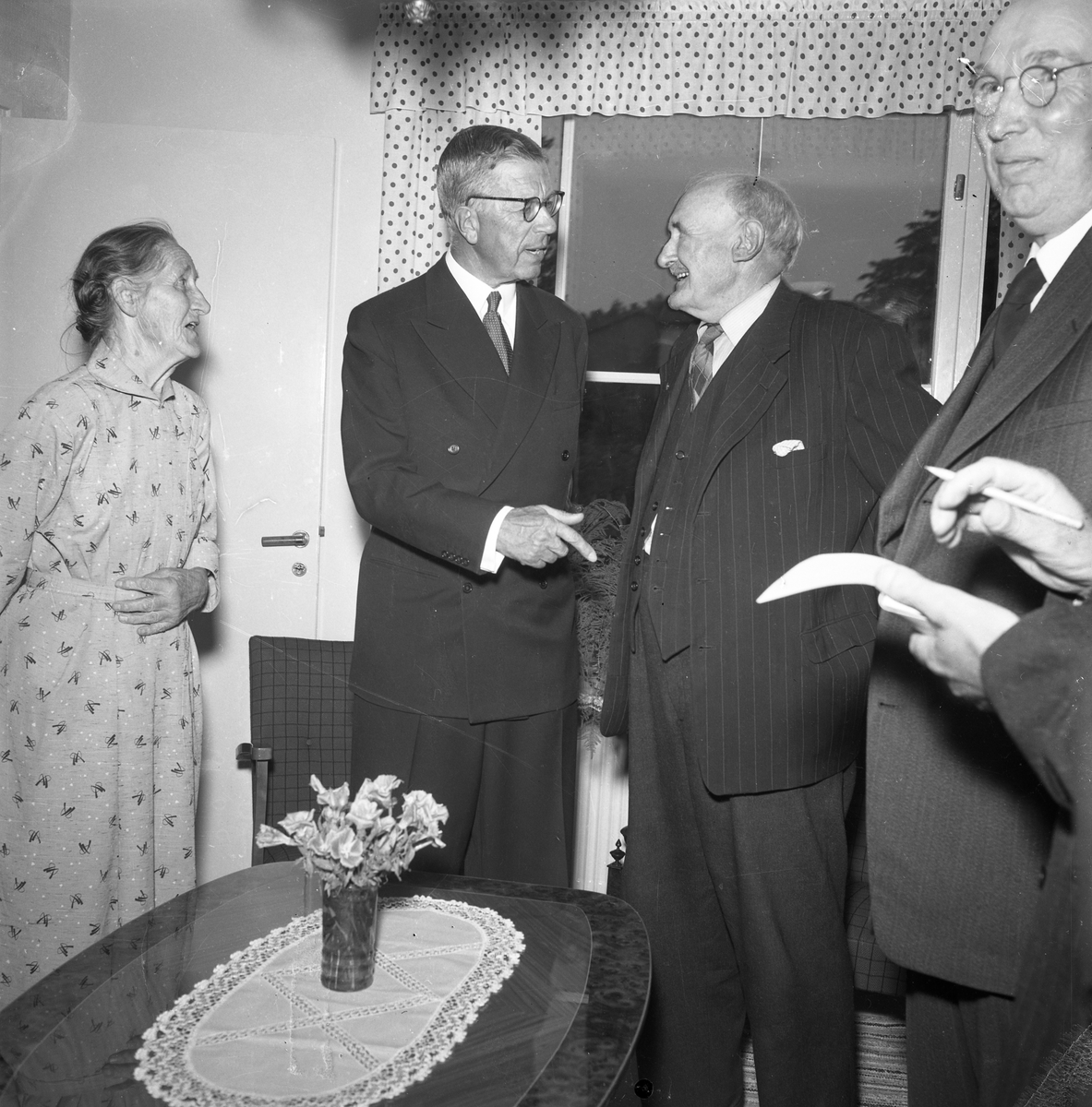 """Konung Gustaf Vl Adolf är på Eriksgata. Här besöker han det första pensionärshemmet i kvarteret Stabbaren. Det äldre paret, som får kungligt besök, är Albertina och Oscar Teodor Carlsson (""""Bom-Calle""""). De är föräldrar till stadsfullmäktiges ordförande, Jonas Carlsson och därmed fotograf Reinhold Carlssons farmor och farfar. Längst till höger ses Gustaf Johansson, (""""Murar-Gustaf""""). Pensionärshemmet räknas som ett av de modernaste i landet. Här finns tolv lägenheter om ett rum och kokvrå för 45 kronor i månaden och sex lägenheter om två rum med kokvrå för 60 kronor i månaden. El och vatten ingår i hyran. För värdskapet, under konungens besök, svarade stadsfullmäktiges ordförande Jonas Carlsson och kommunalborgmästare Danliel Ekelund. Den organisationskommitté som ansvarade för arrangemangen, hade hos drätselkammaren begärt en summa av 3000 kronor för att täcka kostnaderna vid kungabesöket. Beloppet beviljades.  Tiden för kungens besök var beräknad till 130 minuter."""