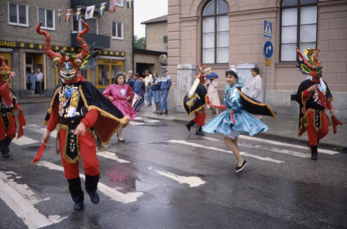Arbogakarnevalen pågår. Paraden har nått fram till Hökenbergs gränd. Uppklädda dansare i regnet. I hörnet, i lika dana regnjackor, står Lotta Winkler Yngve och Olof Yngve. I bakgrunden, till vänster, ses Sandbergs herrekiperingen på Nygatan.