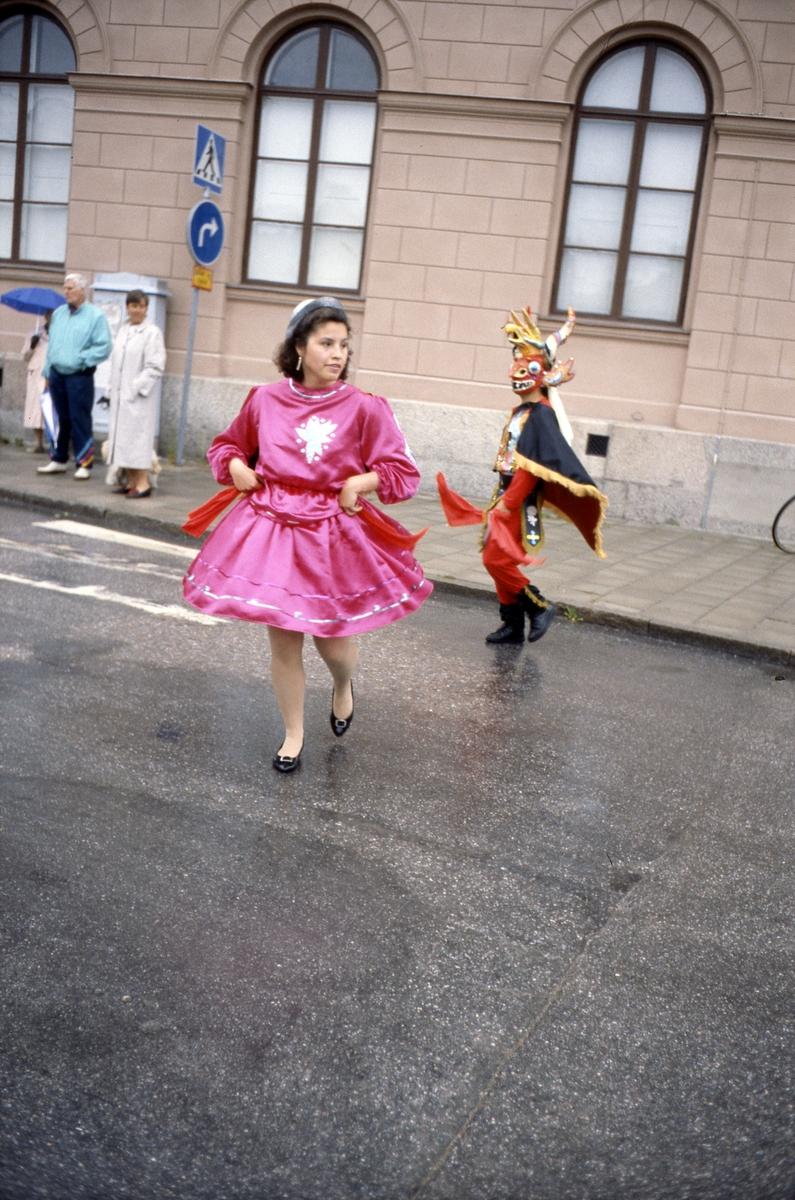 Arbogakarnevalens parad har nått Hökenbergs gränd. Dansare iklädda folkdräkt dansar på den regnvåta gatan. Mannen iklädd ljusblå jacka är Per-Erik Bruksner. Byggnaden är Nikolai skola/Nikolai Kulturhus.