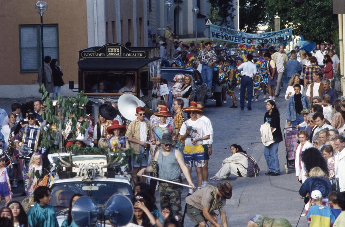 Arbogakarnevalen. Paraden har nått Rådhusgatan. Bilar, dansare och orkestrar. Mitt i bild ses Arboga Blåsorkester iklädda sombreros. Bostadsbolaget Lunds deltar med sin gamla bil. Publiken kantar gatan.
