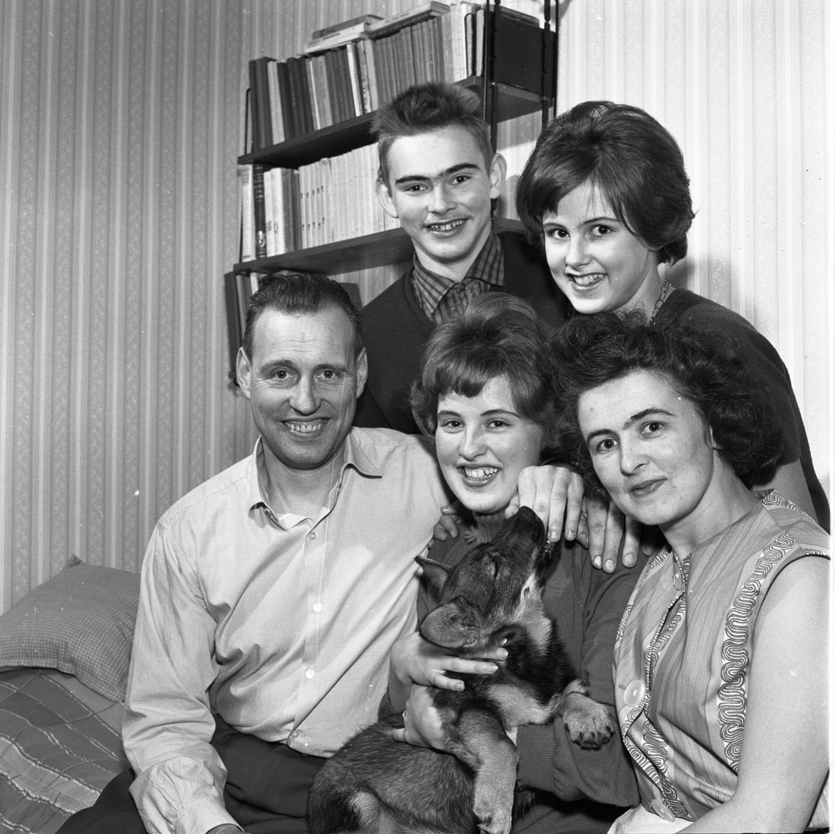 Här ses 1962 års Lucia, Britt-Marie Gustavsson, tillsammans med sin familj; Pappa Max, mamma Britta, bror Tore och syster Maj-Britt. Britt-Marie har en hund i sitt knä. Bakom familjen syns en bokhylla full av böcker.