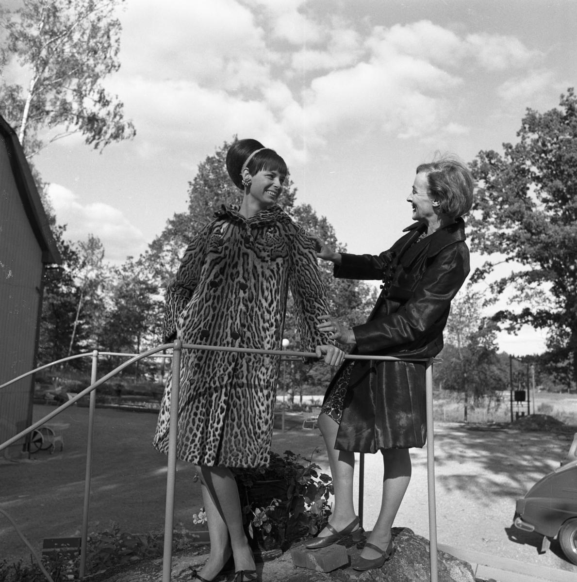 Mannekäng visar en djurmönstrad kappa. Bredvid står Britt-Marie Utterström från Ateljé Touché. Britt-Marie drev ateljen tillsammans med Marianne Rosenkvist.