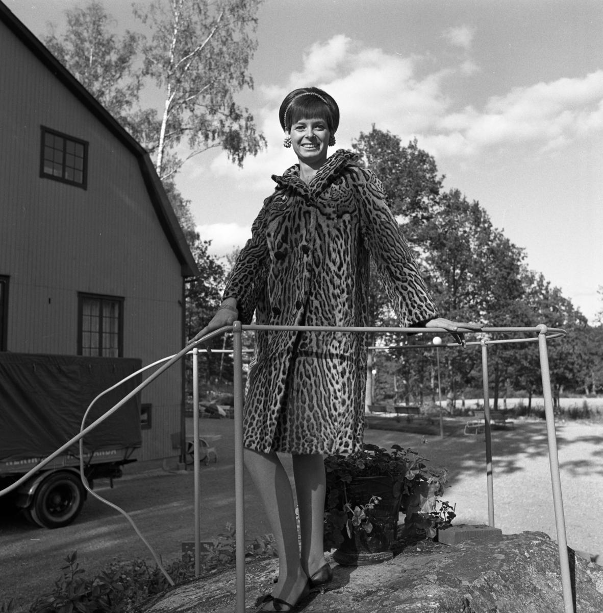 Mode. En kvinna visar en djurmönstrad kappa. Den kan vara från Ateljé Touche